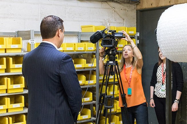 fional filming with barry back head in factory within news story